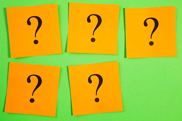 Five Question Marks  Orange on Green Background stock photo