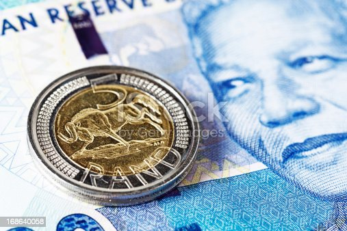 Close-up of a Five Rand coin resting on a new South African Hundred Rand banknote, featuring the smiling face of iconic statesman Nelson Mandela.