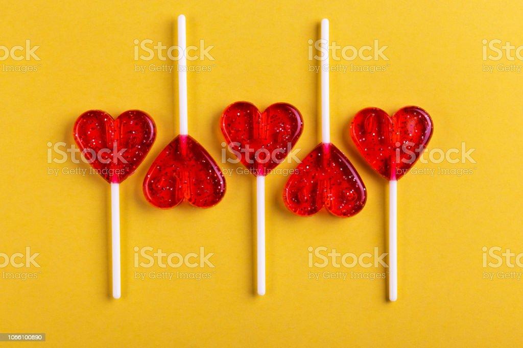 Fünf rote süße leckere Lutscher in Form von Herzen auf leuchtend gelbem Hintergrund. St. Valentinstag – Foto