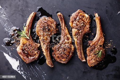 Roasted lamb ribs with spices on black marble background