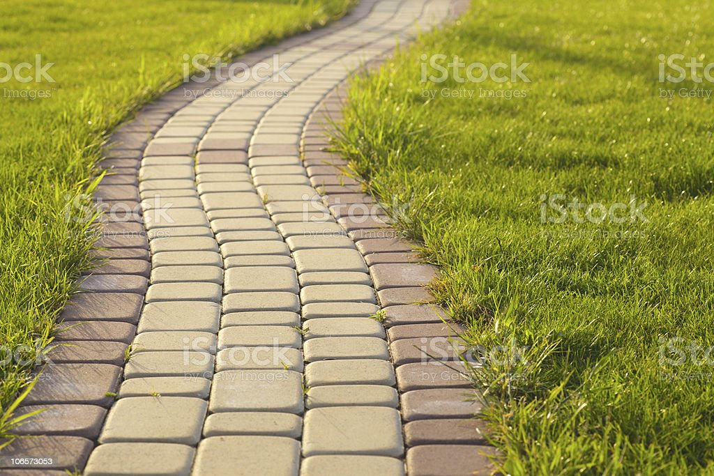 A five rowed brick path next to green grass stock photo