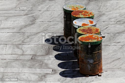 Five rusty industrial steel drums cast their shadows on an urban rooftop.