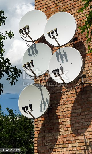 Five satellite dish antennas are mounted on the wall of a brick building.