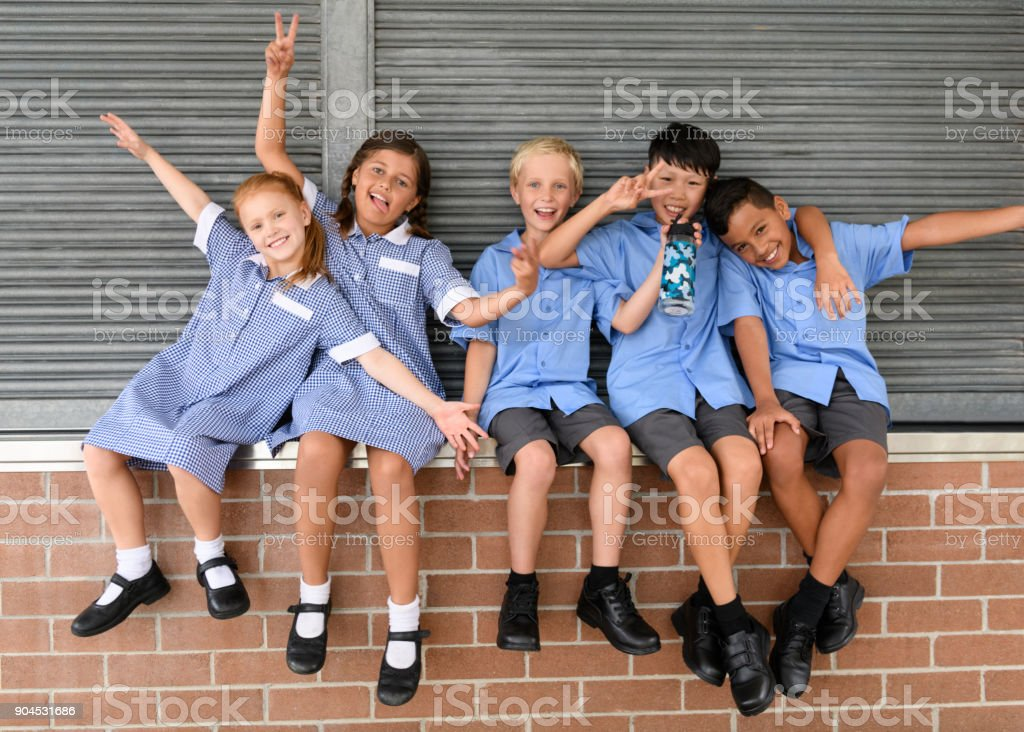 Five school friends sitting on brick wall pulling faces and smiling towards camera stock photo