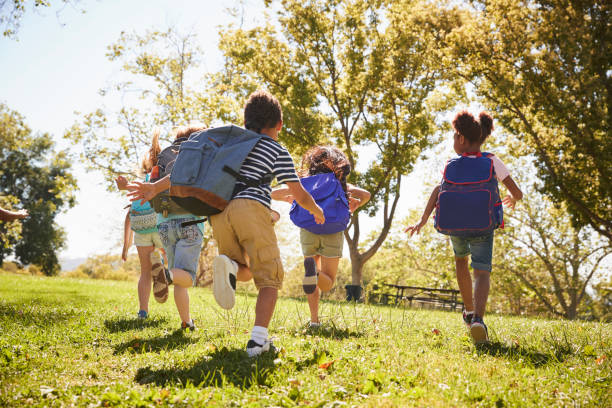 Five school kids running in a field, back view, close up Five school kids running in a field, back view, close up school exteriors stock pictures, royalty-free photos & images
