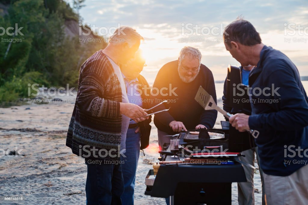 Five seniors brothers cooking fish on BBQ on the beach stock photo
