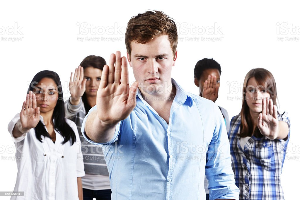 Five serious young people hold up hands indicating Stop stock photo