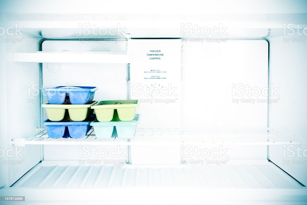 Five sets of ice cube trays in a freezer stock photo