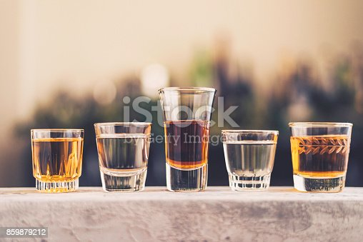 Five shot glasses filled with a variety of alcohol