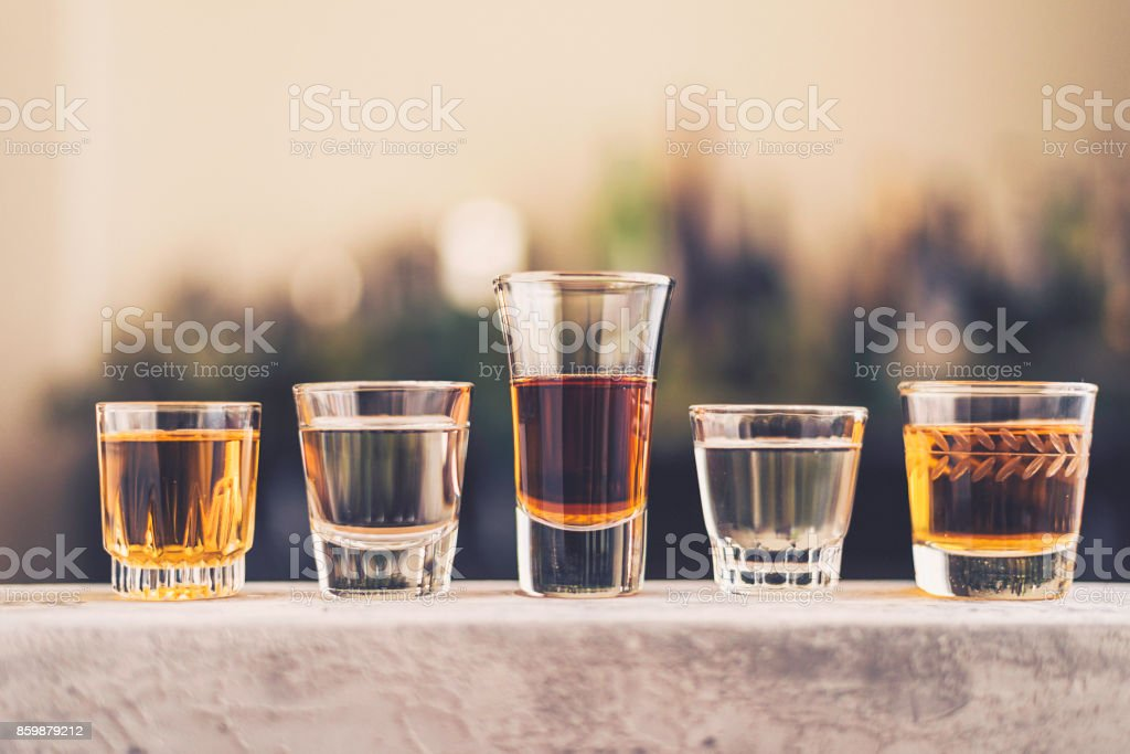Five shot glasses filled with a variety of alcohol stock photo