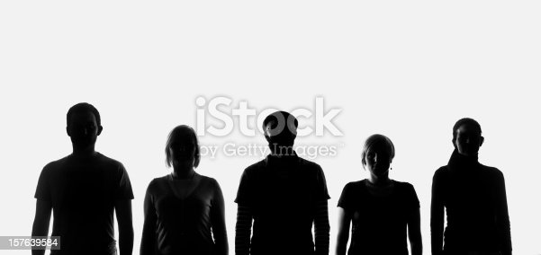 Five silhouettes of people standing in a row and posing for a picture. Studio shot on the white background.