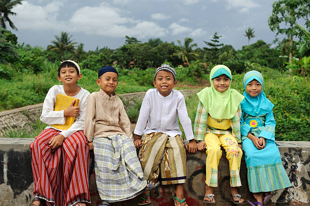 Five smiling young Muslim kids sitting on a brick wall Group of Muslim kids, sitting on bridge indonesian ethnicity stock pictures, royalty-free photos & images