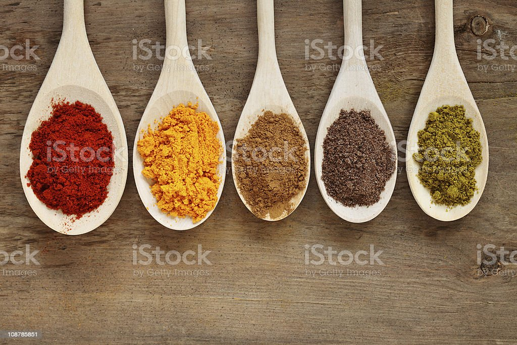 Five spoons with different colored spices royalty-free stock photo