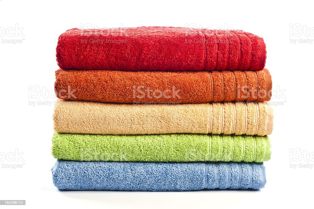 Five stacked, multicolored bath towels isolated on white background stock photo