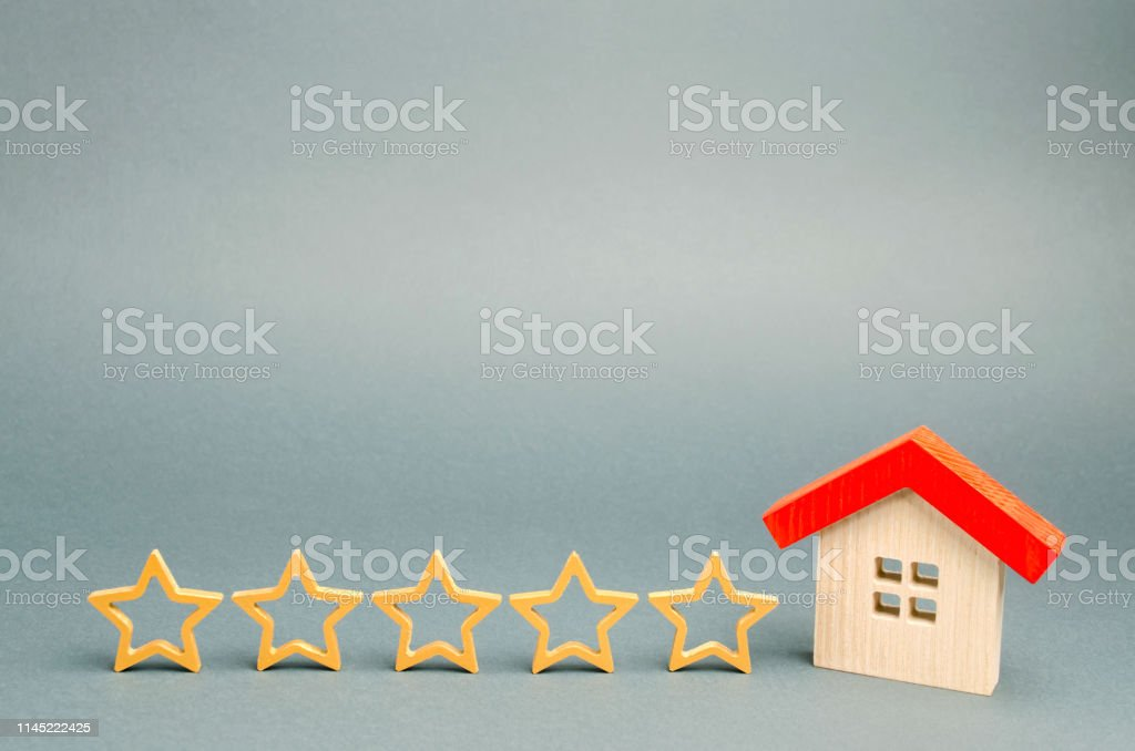 Five stars and a wooden house on a gray background. The concept of...