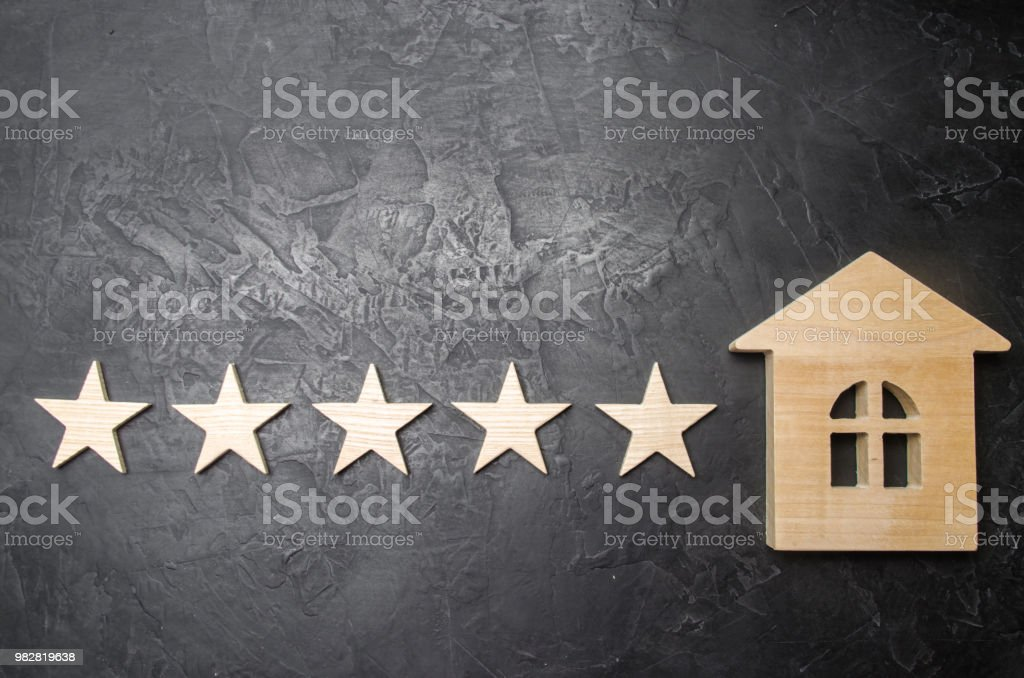 Five stars and a wooden house on a gray concrete background. The concept of the best housing, luxury apartments VIP class. The best service and universal recognition, a high score. Success. stock photo