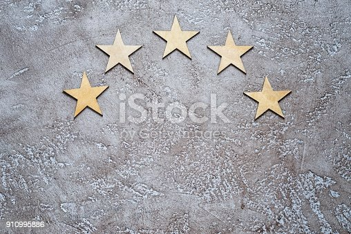 istock Five stars in half round on cement background, top view with copy space. 910995886