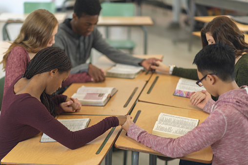 Five students in a classroom are sitting with their desks pushed together. They are holding hands in a circle and have their heads bowed in prayer. There are bibles open on their desks.
