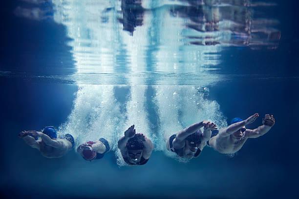 fünf schwimmer springen zusammen in wasser- unterwasser - koordination stock-fotos und bilder