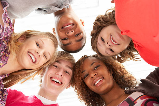 Five Teenage Friends Looking Down Into Camera Five Teenage Friends Looking Down Into Camera Smiling teenagers only stock pictures, royalty-free photos & images