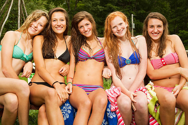 cinq jeunes filles assis sur une table de pique-nique de bikinis - fille 16 ans photos et images de collection