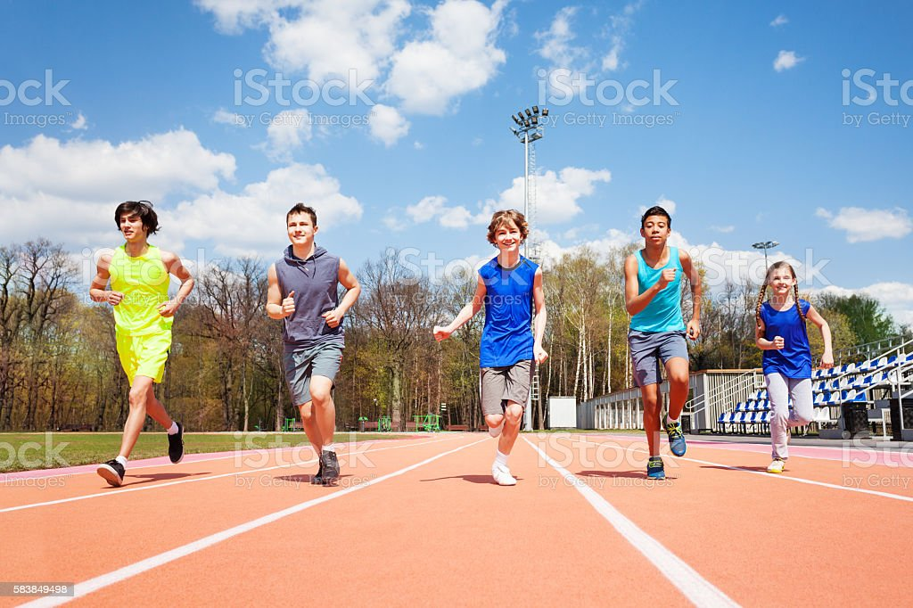 Five teenage sprinters running together on a track - foto de stock