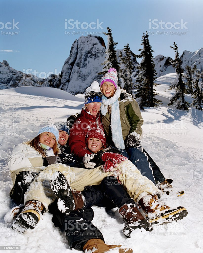 Five teenagers (15-18) sitting in snow, smiling, portrait stock photo