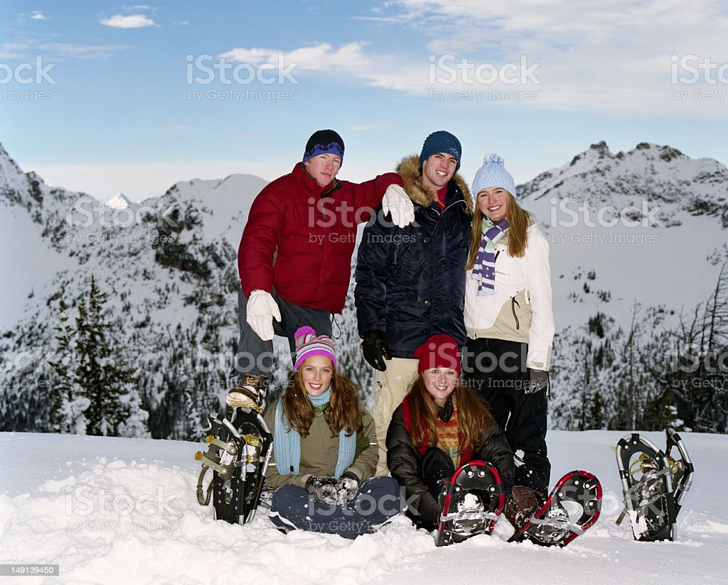 Five teenagers (15-18) with snowshoes on snowy landscape, portra stock photo