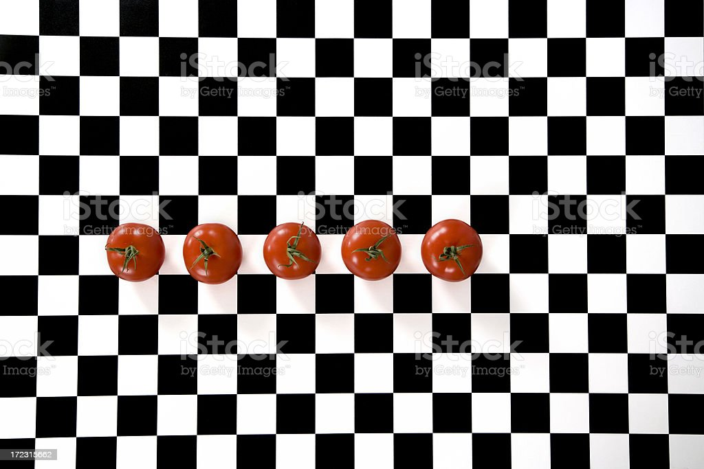 five tiny tomatoes on a checkerboard royalty-free stock photo