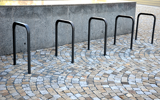 905087856 istock photo five wheel stands of black metal bent tube in the shape of a rectangle in front of the retaining wall paving of granite cubes in the city 1256254796