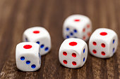 Five white dice shows the number 1 on a wooden table. Five white dice showing one