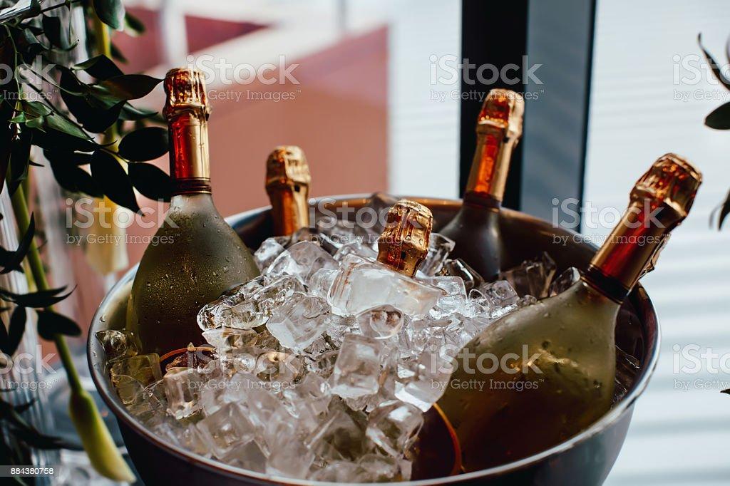 Five wine bottles chill in ice bucket stock photo
