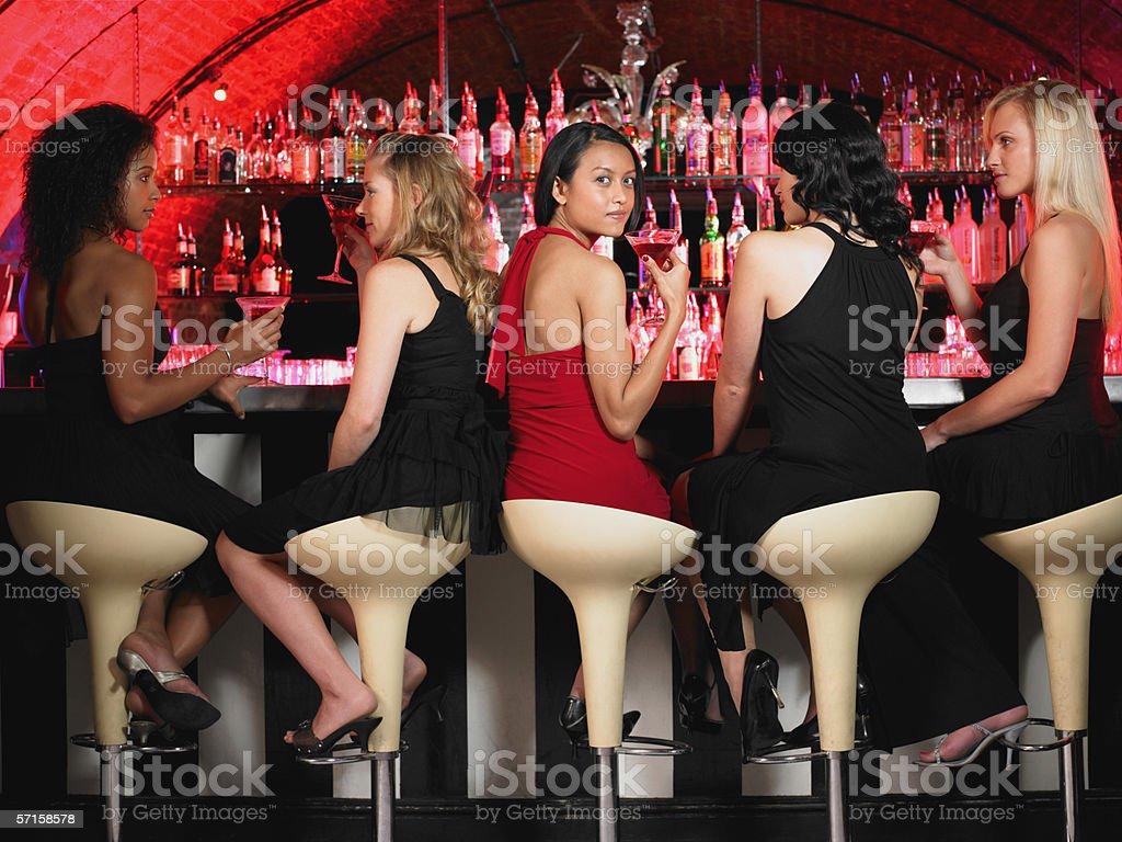Five women sitting at bar stock photo