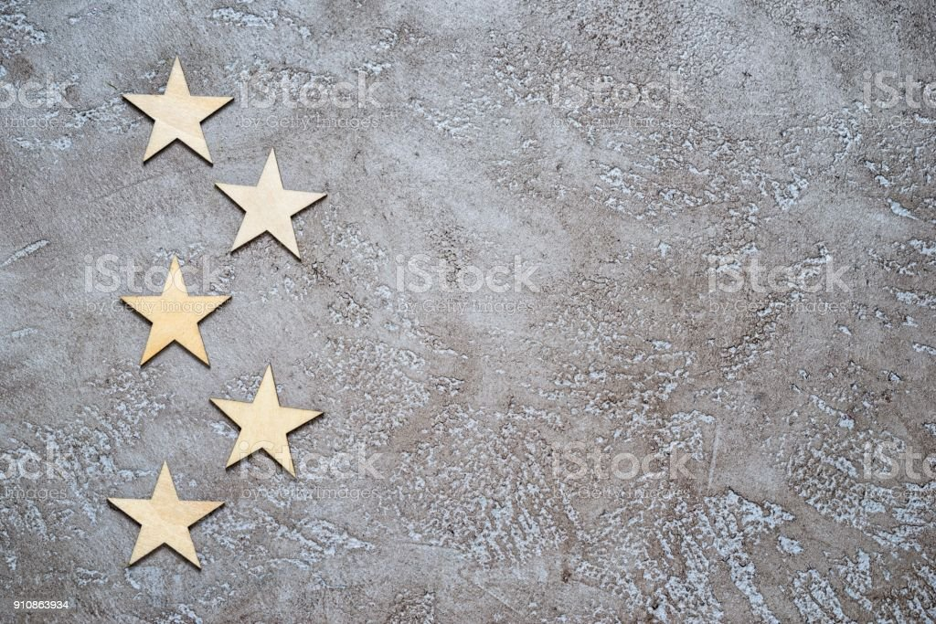five wooden hearts lie zigzag in the form of bullets on the left of a textured neutral cement background with copy space for your text. stock photo