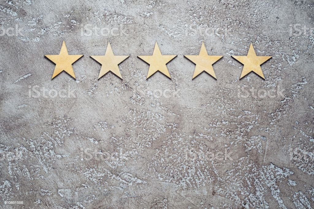 five wooden stars arranged in row on a neutral beige textured cement background, top view with copy space. Best rating customer feedback concept. royalty-free stock photo