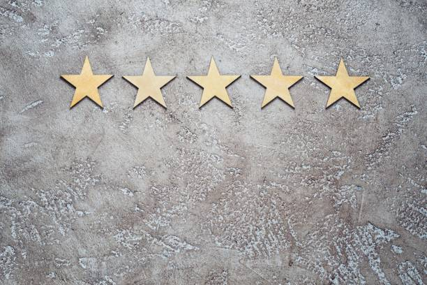 five wooden stars arranged in row on a neutral beige textured cement background, top view with copy space. Best rating customer feedback concept. five wooden stars arranged in row on a neutral beige textured cement background, top view with copy space. Best rating customer feedback concept. first class stock pictures, royalty-free photos & images