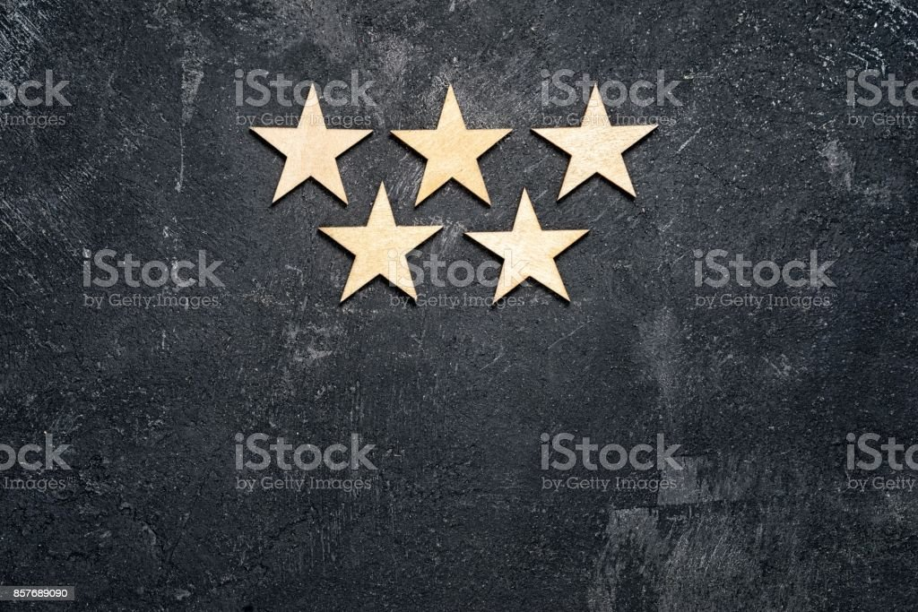 Five wooden stars arranged in two rows, 3 on the top and 2 below, on a dark cement background with copy of the space. Concept of service rating and quality of trade. Top view, copy space for your text stock photo