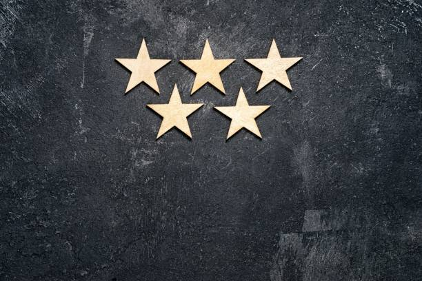 Five wooden stars arranged in two rows, 3 on the top and 2 below, on a dark cement background with copy of the space. Concept of service rating and quality of trade. Top view, copy space for your text Five wooden stars arranged in two rows, 3 on the top and 2 below, on a dark cement background with copy of the space. Concept of service rating and quality of trade. Top view, copy space for your text first class stock pictures, royalty-free photos & images