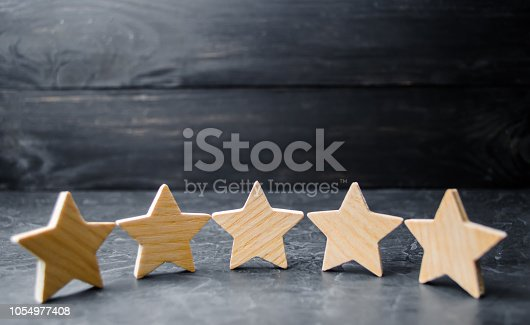 istock Five wooden stars. Get the fifth star. The concept of the rating of hotels and restaurants, the evaluation of critics and visitors. Quality level, good service. selective focus 1054977408