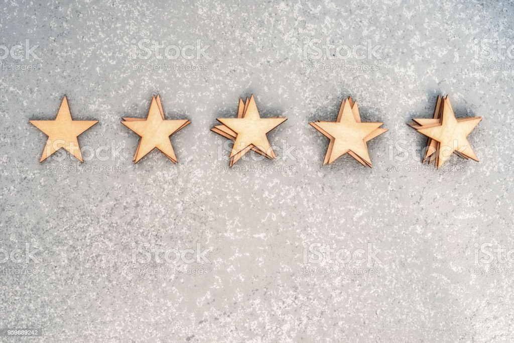 five wooden stars in piles of 1, 2, 3, 4 and 5 pieces on a silver background, top view with copy space stock photo