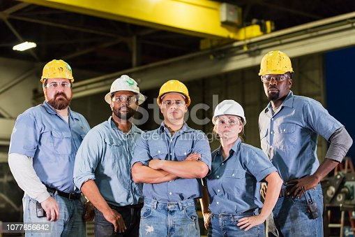 A group of five multi-ethnic workers wearing hardhats and safety glasses, standing in a dark warehouse. The team includes a mature woman in her 40s. They are standing side by side looking at the camera with serious expressions.