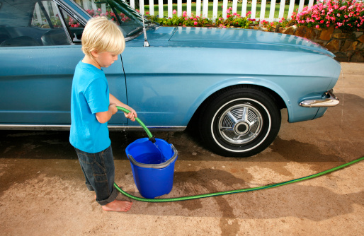 five year old boy washing the car