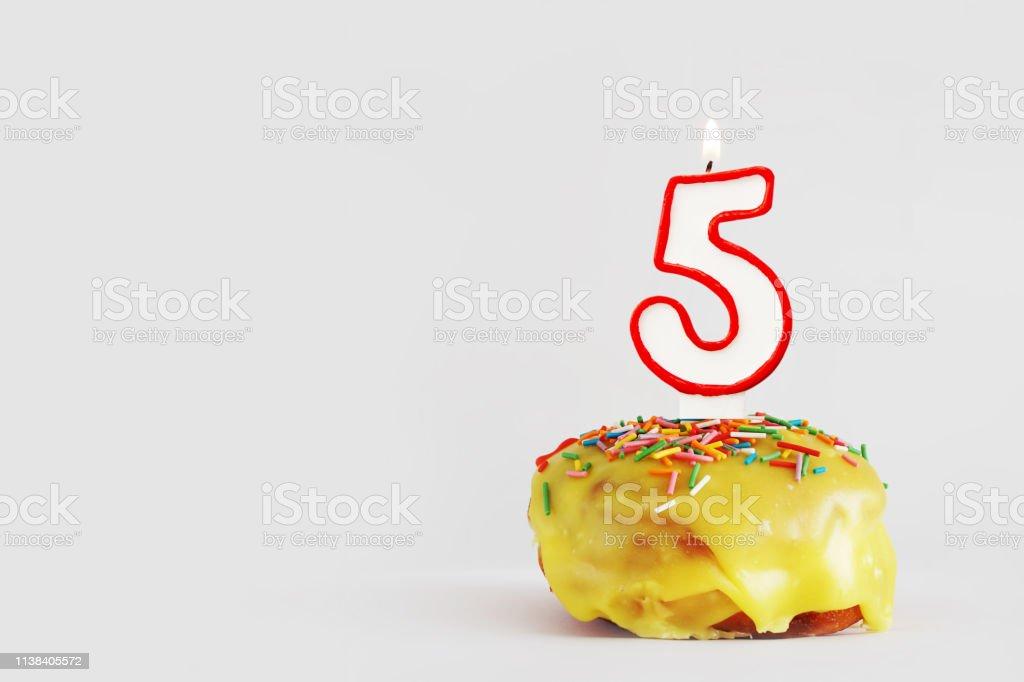 Five years anniversary. Birthday cupcake with white burning candle...