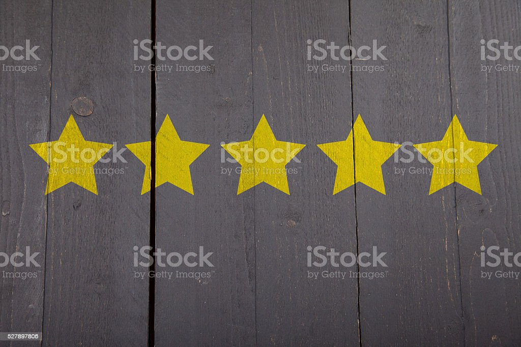 Five yellow ranking stars on black wooden background stock photo