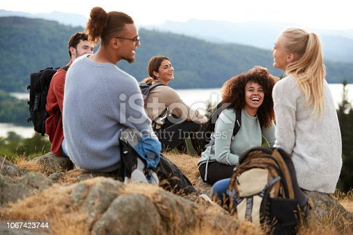 istock Five young adult friends sit talking at the summit after a mountain hike, close up 1067423744