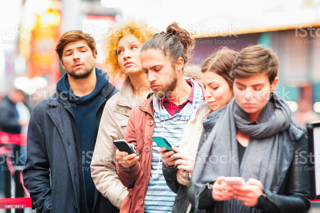 Five young adults waiting in line some using phones stock photo