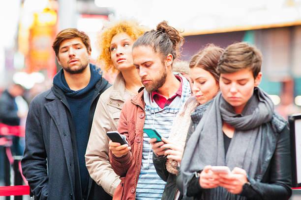 cinq jeunes adultes, faire la queue quelques entreprises utilisant des téléphones - queue photos et images de collection