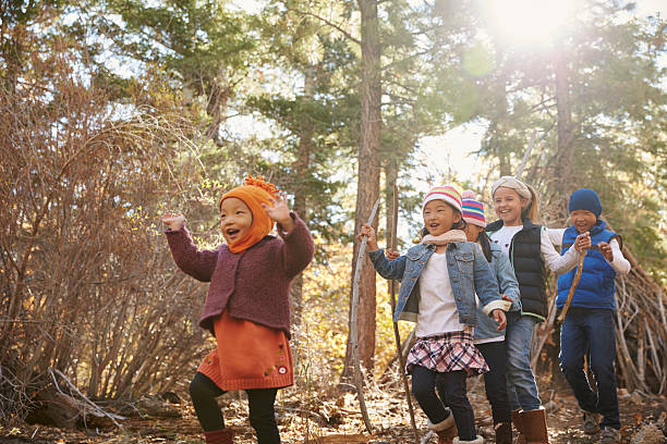 five young children playing together in a forest, - bos spelen stockfoto's en -beelden