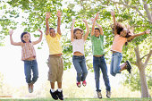 Five young friends jumping outdoors smiling having fun playing around in garden