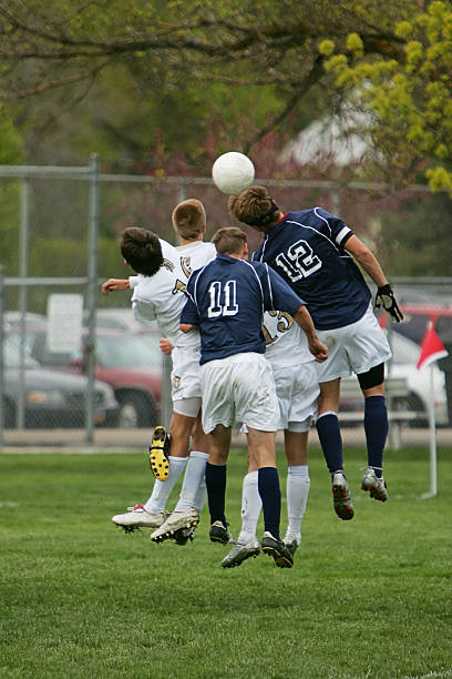 five young male soccer players jump to head ball - head injury stock photos and pictures